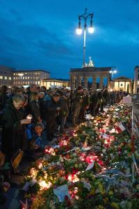 epa05025301 People gather to pay tribute to victims opf the Paris attacks outside the French embassy near the Brandenburg Gate in Berlin, Germany, 14 November 2015. At least 120 people have been killed in a series of attacks in Paris, France on late 13 November 2015, according to French officials. Eight assailants were killed, seven when they detonated their explosive belts, and one when he was shot by officers, police said.  EPA/JOERG CARSTENSEN