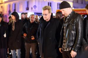 epa05025657 Members of Irish rock band U2 (L-R) Bono (L) and David Howell Evans lay flowers at a tribute to the victims of the Paris terror attacks, outside the Bataclan theatre in Paris, France, 14 November 2015. At least 120 people have been killed in a series of attacks in Paris, France on late 13 November 2015, according to French officials. Eight assailants were killed, seven when they detonated their explosive belts, and one when he was shot by officers, police said.  EPA/MALTE CHRISTIANS
