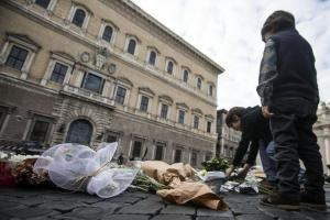 Flowers are laid in front of the French embassy in Rome, Saturday, Nov. 14, 2015. French police on Saturday hunted possible accomplices of eight assailants who terrorized Paris concert-goers, cafe diners and soccer fans with a coordinated string of suicide bombings and shootings in France's deadliest peacetime attacks. ANSA/ANGELO CARCONI