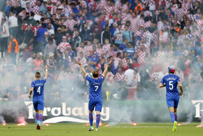epa05373325 Croatia players (L-R) Ivan Perisic, Ivan Rakitic and Vedran Corluka appeal to Croatia supporters (background) after flares were thrown onto the pitch during the UEFA EURO 2016 group D preliminary round match between the Czech Republic and Croatia at Stade Geoffroy Guichard in Saint-Etienne, France, 17 June 2016. (RESTRICTIONS APPLY: For editorial news reporting purposes only. Not used for commercial or marketing purposes without prior written approval of UEFA. Images must appear as still images and must not emulate match action video footage. Photographs published in online publications (whether via the Internet or otherwise) shall have an interval of at least 20 seconds between the posting.) EPA/YURI KOCHETKOV EDITORIAL USE ONLY