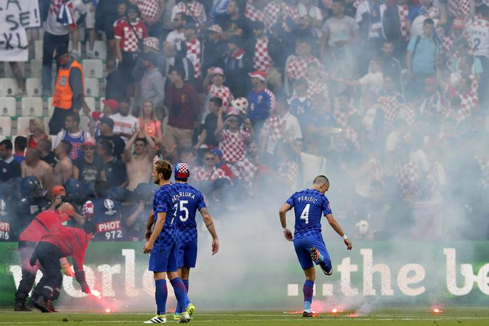 epa05373309 Croatia players (C) and ground staff (L) try to remove flares thrown onto the pitch by Croatia supporters (background) during the UEFA EURO 2016 group D preliminary round match between the Czech Republic and Croatia at Stade Geoffroy Guichard in Saint-Etienne, France, 17 June 2016. (RESTRICTIONS APPLY: For editorial news reporting purposes only. Not used for commercial or marketing purposes without prior written approval of UEFA. Images must appear as still images and must not emulate match action video footage. Photographs published in online publications (whether via the Internet or otherwise) shall have an interval of at least 20 seconds between the posting.) EPA/YURI KOCHETKOV EDITORIAL USE ONLY